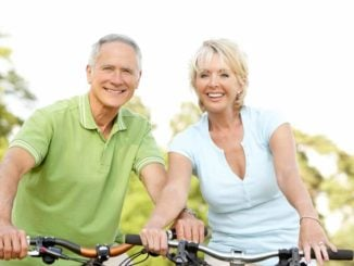 smiling senior couple riding a bike