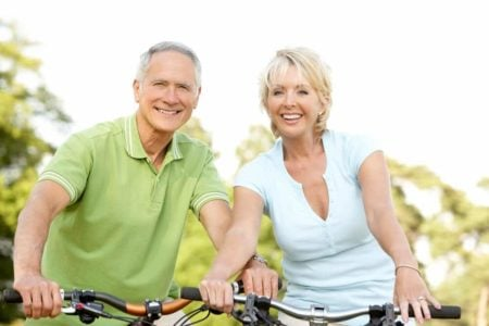 smiling senior couple riding a bike