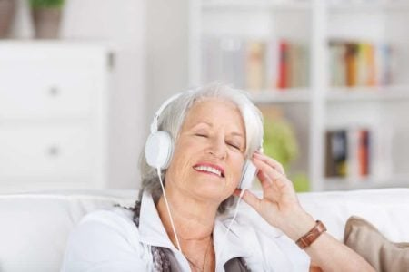 senior woman smiling and enjoying music through her noise cancelling headphones