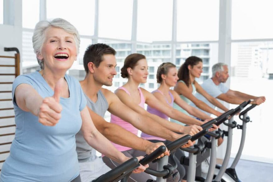 senior woman giving thumbs up to her spinning class