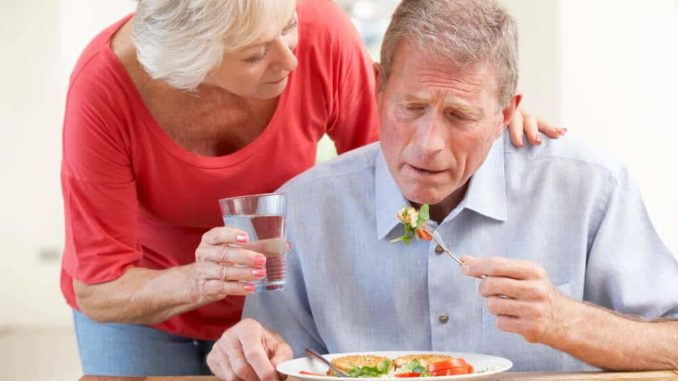 senior woman helping her husband with dementia eat