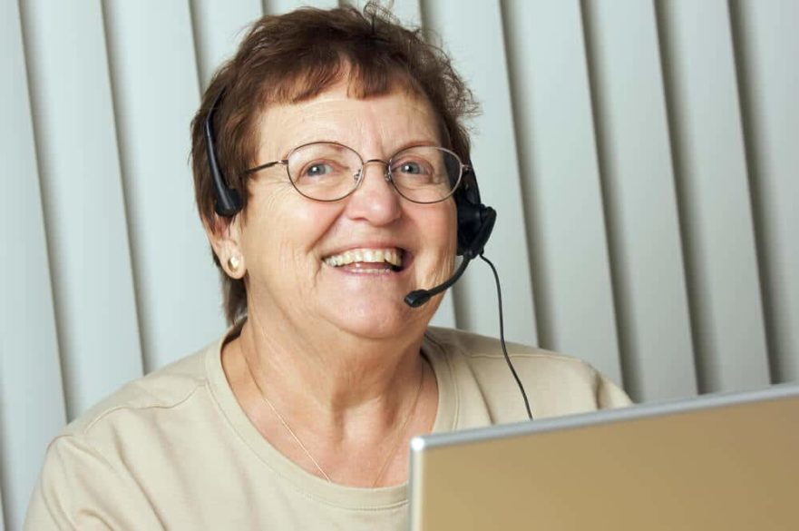 smiling senior woman using a phone headset for seniors that is comfortable and easy to use.