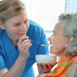 caregiver feeding a elderly woman who is wearing a stylish bib for adults