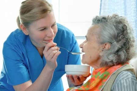 caregiver feeding a elderly woman who is wearing a stylish bib for adults