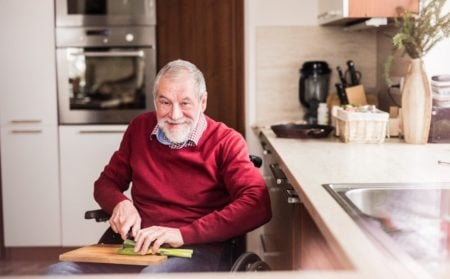 man with dementia in wheelchair chopping vegetables