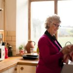 senior woman with dementia drying dishes with kitchen appliances in the background
