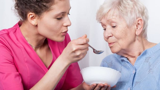 woman feeding a senior with dementia who needs a dignity bib