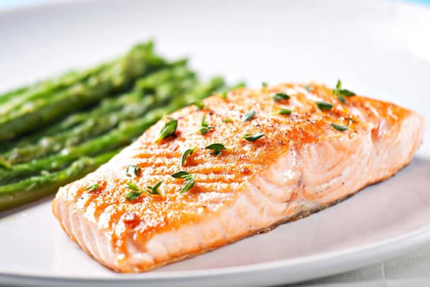 piece of salmon with asparagus on a white plate