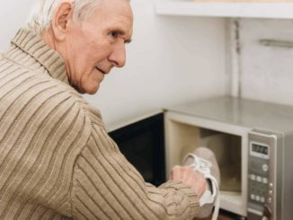 man with dementia putting shoe in the microwave