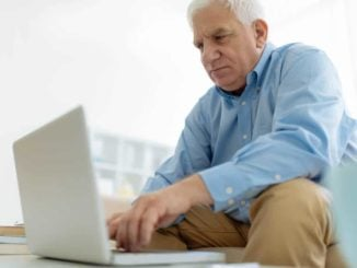 senior man using a computer on a coffee table
