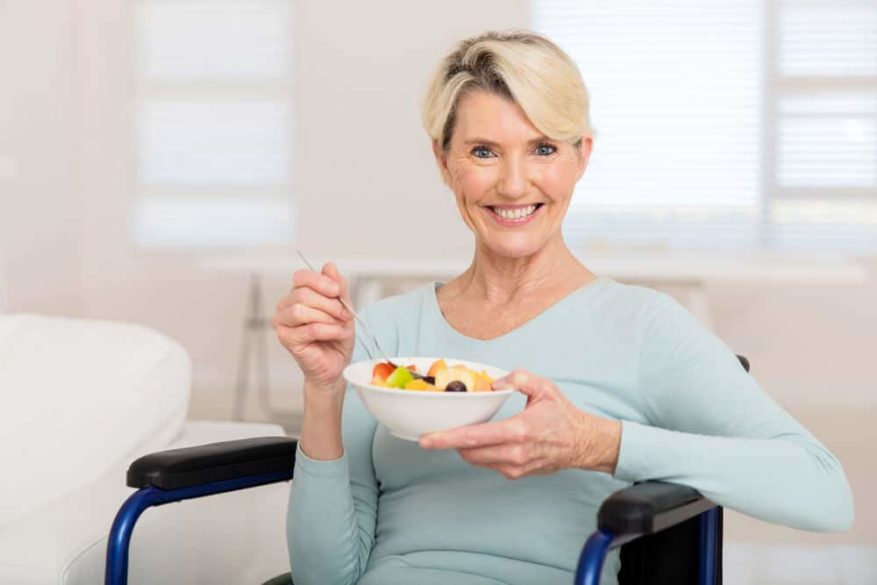 senior woman with dementia eating a bowl of fruit salad