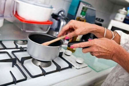 senior hands stirring a pot on a cooking stove