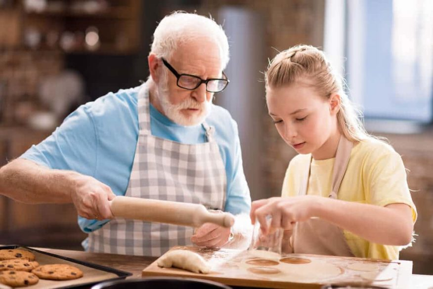 senior man with dementia cooking with his grandaughter
