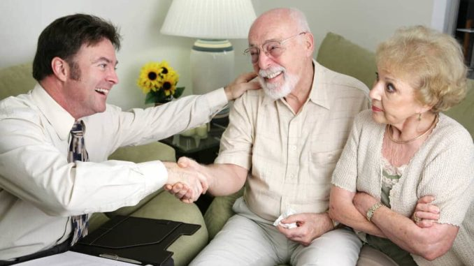 salesman taking to seniors with skeptical wife looking on