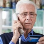 senior man giving credit card info to scammer