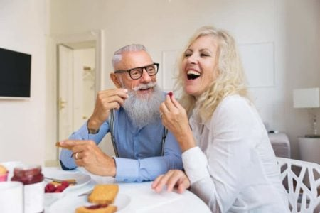 daughter enjoying snacks with her elderly father