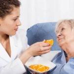 nurse feeding elderly woman an orange