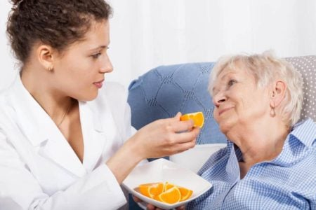 nurse feeding elderly woman an orange