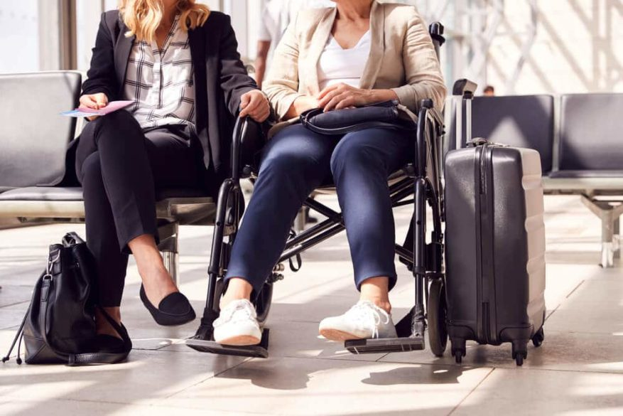 woman sitting in a wheelchair at airport gate waiting on a flight