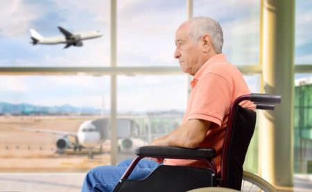 senior man at airport waiting to take wheelchair on airplane