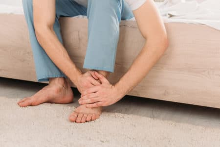 man rubbing his feet to relieve arthritic foot pain
