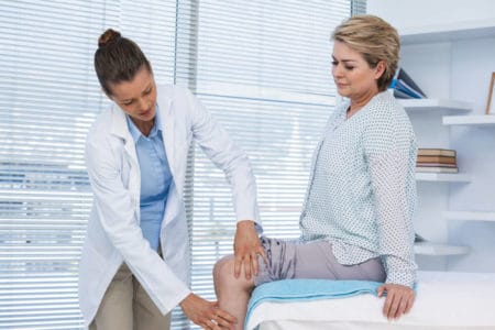 woman having her knee arthritis examined by a doctor