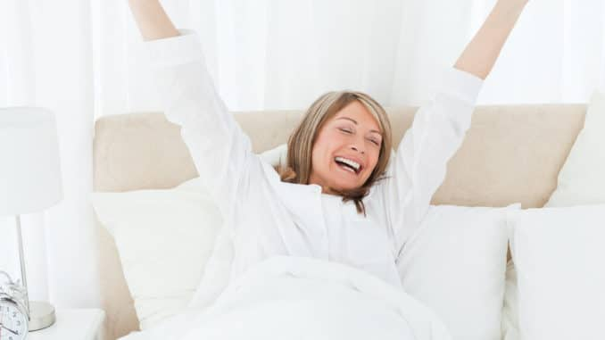 woman smiling after waking up with a good night's sleep