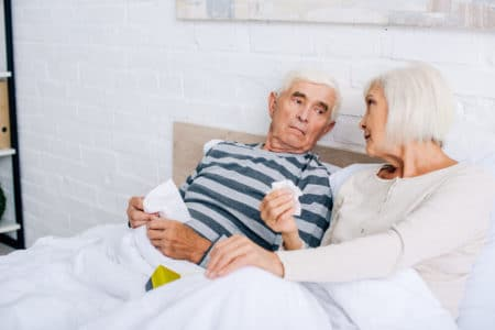 woma talking to her elderly husband in bed