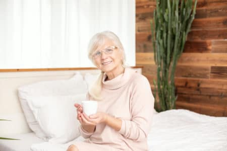 senior woman smiling in bed while drinking coffee