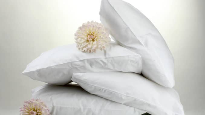 group of fluffy white pillows against a white background