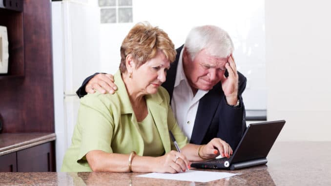 senior couple looking at credit card bills on the computer