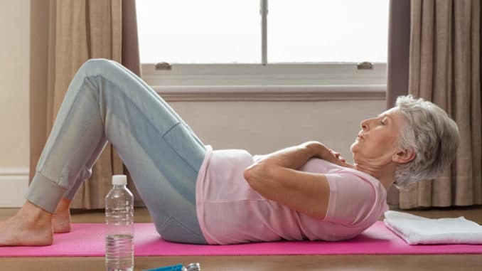 senior woman doing situps as exercise to relieve arthritic knee pain