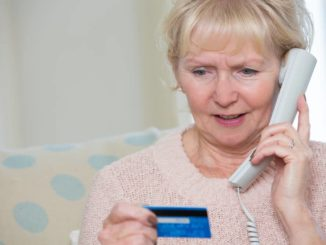 senior woman giving out credit card over phone