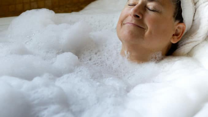 woman smiling and relaxing in a hot bath
