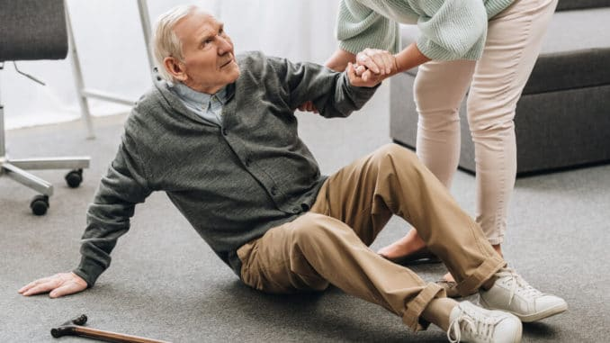 senior woman helping husband up after he had a fall