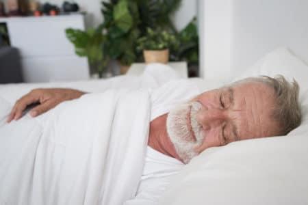 senior man sleeping on back to alleviate arthritic knee pain