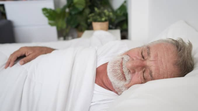 senior man sleeping on back to alleviate arthritic knee pain