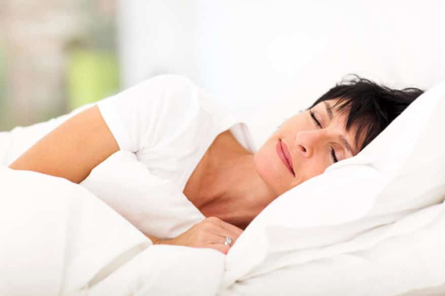 woman sleeping peacefully in bed of white sheets and pillows