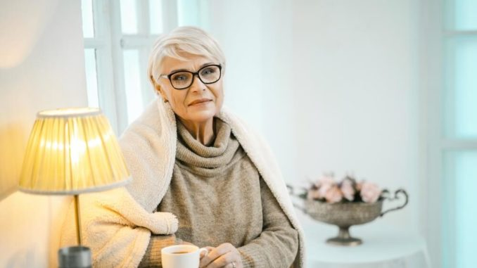 elderly woman keeping warm under blanket and cup of hot tea