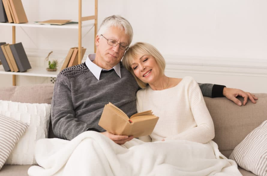 Happy senior couple reading book together covered with an electric blanket, spending time at home