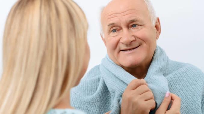 elderly man curled up in blanket