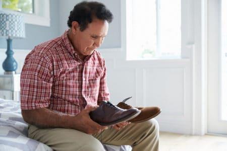 senior man choosing proper footwear for him to prevent falls