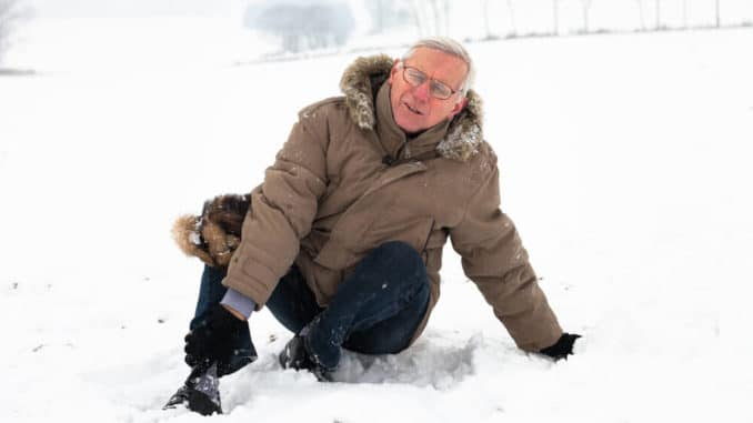 senior man getting up after a fall in the snow