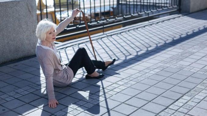 senior woman sitting on sidewalk after a fall