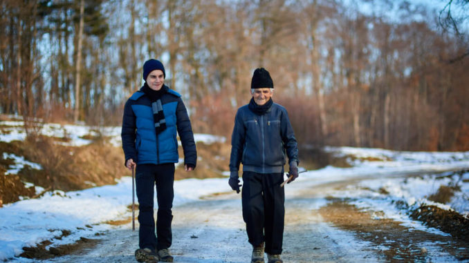 man and son walking in park during winter