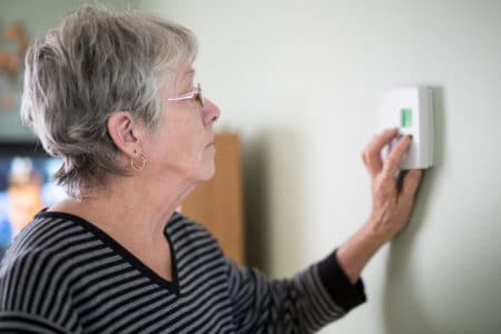 senior woman pushing buttons on thermostat for the elderly