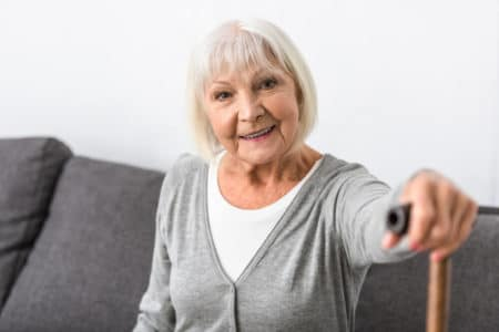 senior with limited mobility showing her cane to camera cane