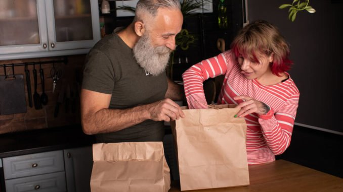 senior couple with bags of take out food