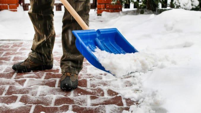 senior man shoveling snow in the winter