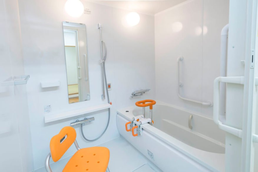 shower chair sitting next to tub in the bathroom